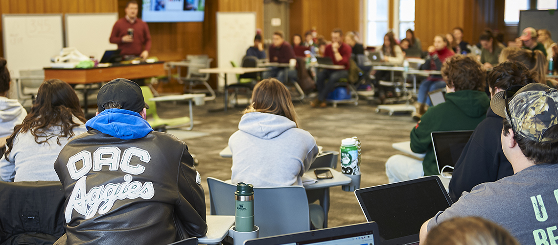 Students sitting in a classroom. One student wearing an OAC aggies jacket.