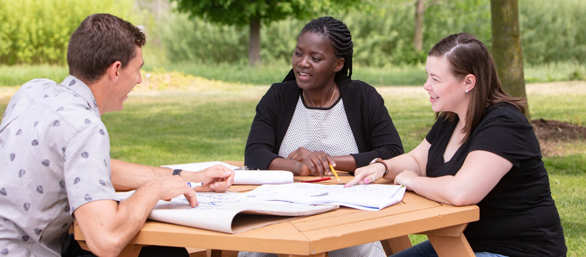 Three students sit at picnic table and discuss plans in front of them