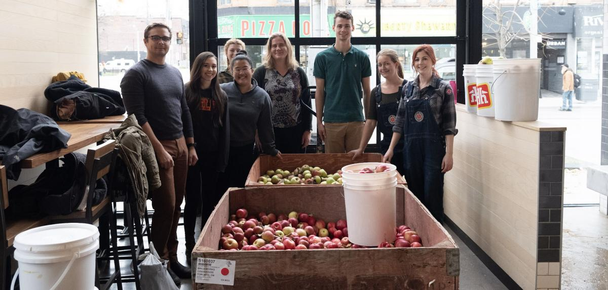 A group of people stand in front of a barrel of apples.