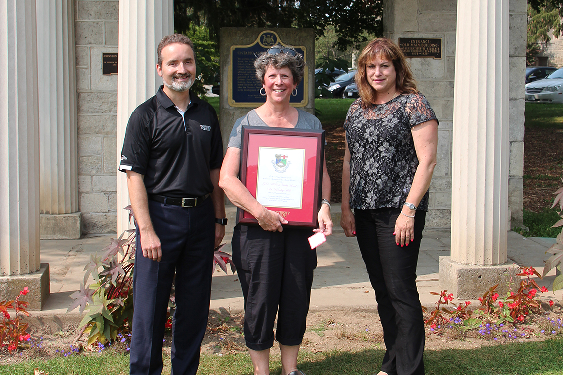 Anna DeMarchi-Meyers, Bev Hale and Rene Van Acker pose outside with framed certificate