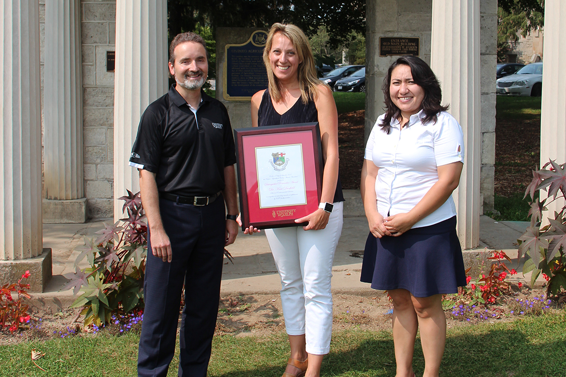 Rocio Morales Rayas, Kari Dunfield and Rene Van Acker pose outside with framed certificate