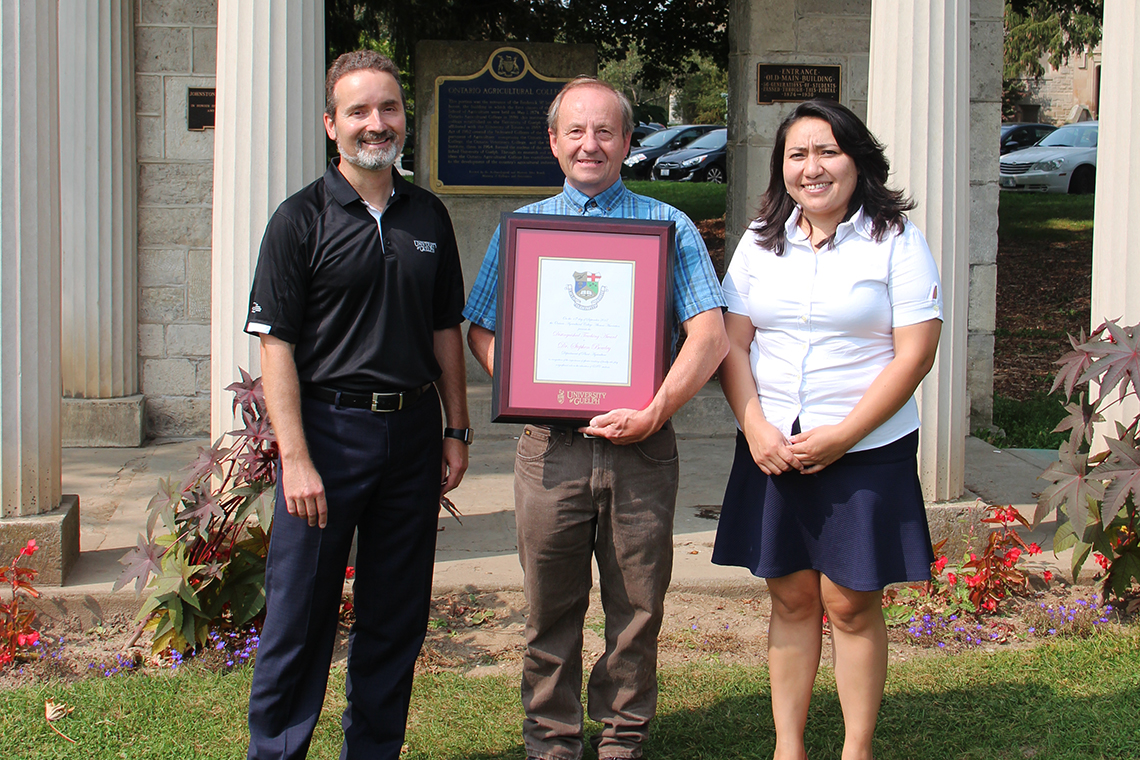 Rocio Morales Rayas, Stephen Bowley and Rene Van Acker pose outside with framed certificate