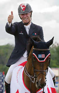 "Ian Millar on horse wearing helment and giving a ""thumbs up"""