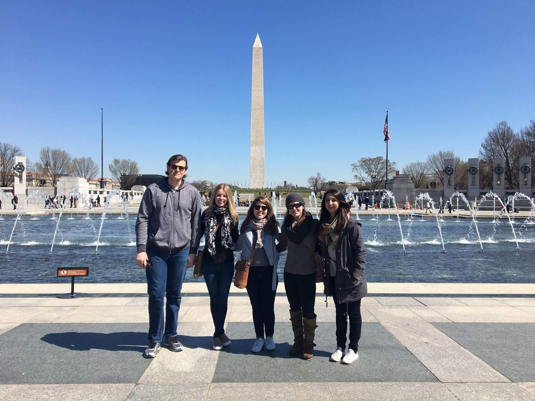 Five students stand in front of National WWII Memorial at the National Mall, water fountains in background