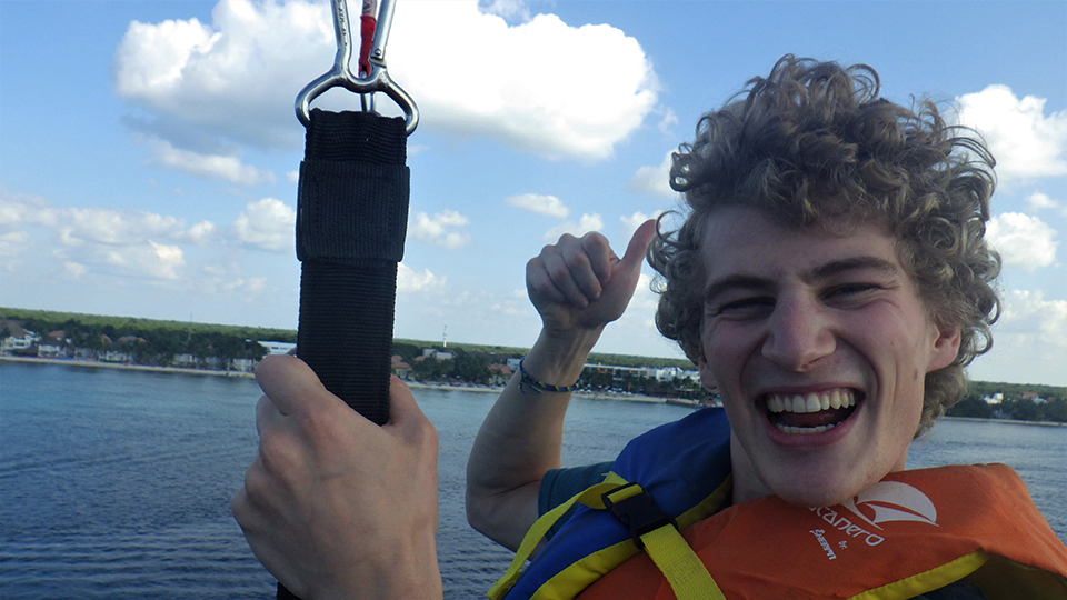 Owen smiling and giving a thumbs up while parasailing.