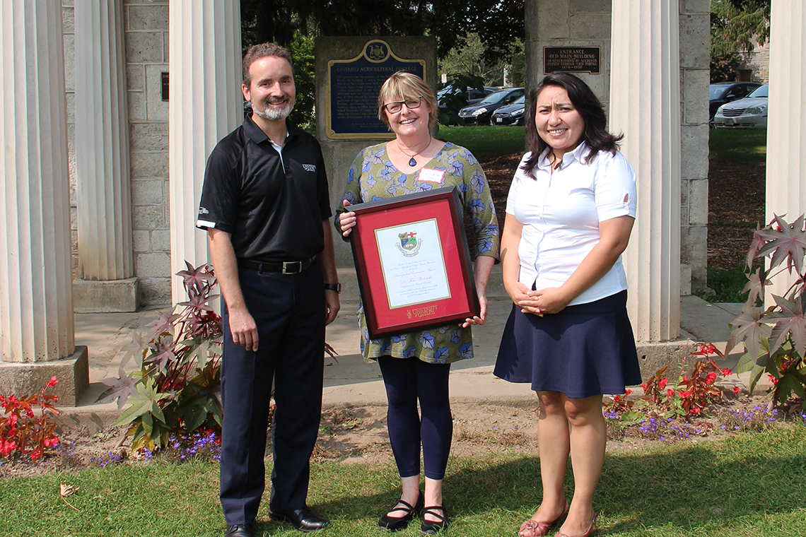 Rocio Morales Rayas, Tina Widowski and Rene Van Acker pose outside with framed certificate