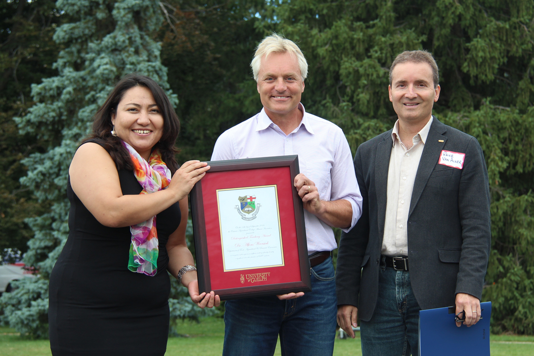 Rocio Morales Rayas, Alfons Weersink and Rene Van Acker pose outside with framed certificate