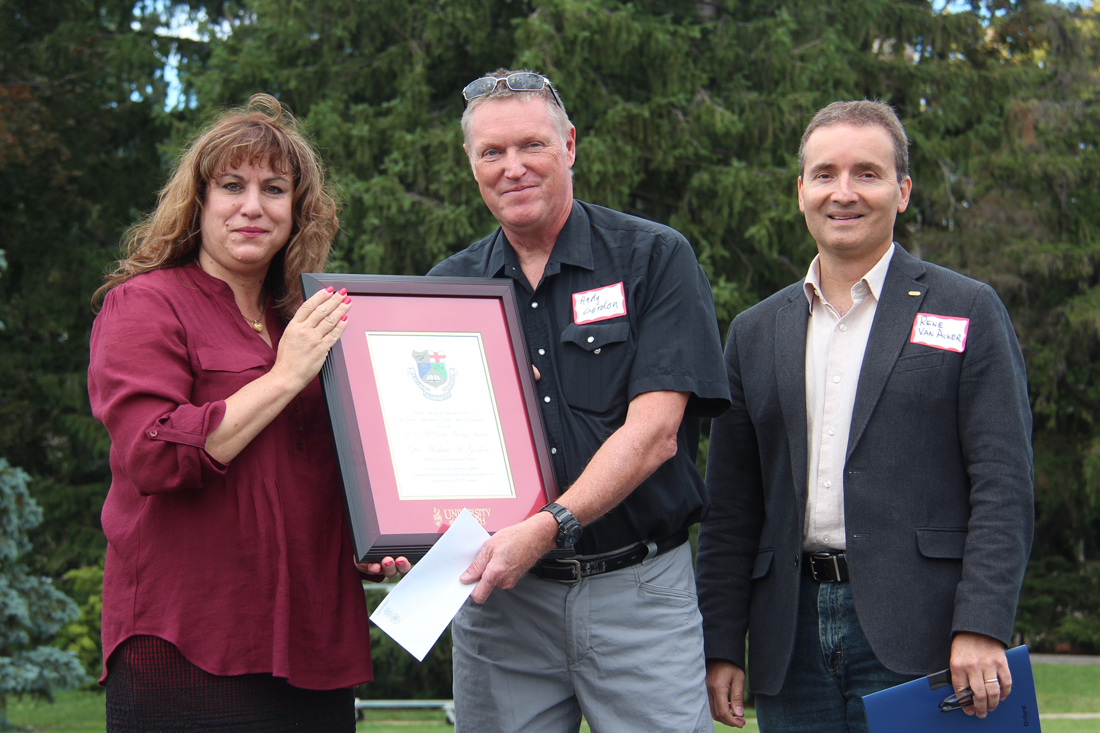 Anna DeMarchi-Meyers, Andy Gordon and Rene Van Acker pose outside with framed certificate