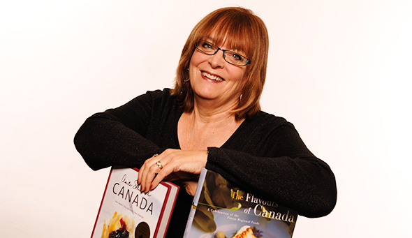 Anita Stewart poses with two cookbooks, Anita Stewart's CANADA and the Flavours of Canada.