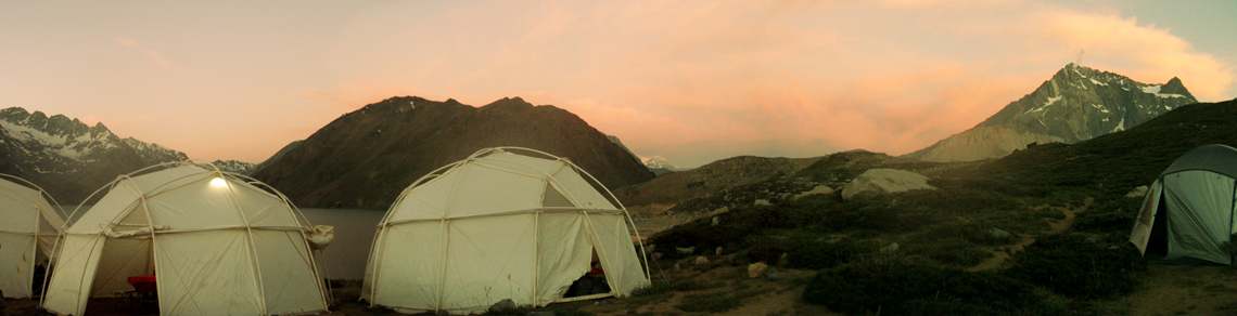 White tent structures on rocky terrain infront of pink misty sky