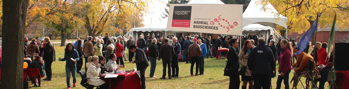 Large Dept of Animal Biosciences banner hanging outside, with many people standing around and large tent in background.