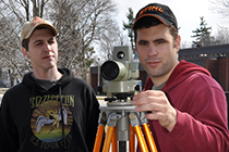 Two environmental management students take measurements.