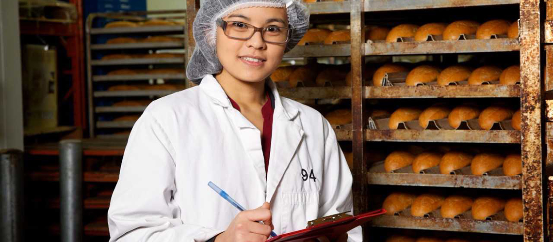 Student with clip board in hand inspects bread.