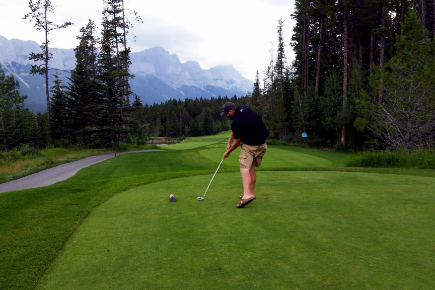 Gary plays golf on a course in the mountains.