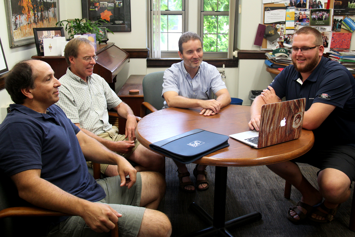 Gary sits with his three advisors at a circle table, showing information on laptop.