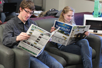 Two students read the Ontario Farmer newspaper.