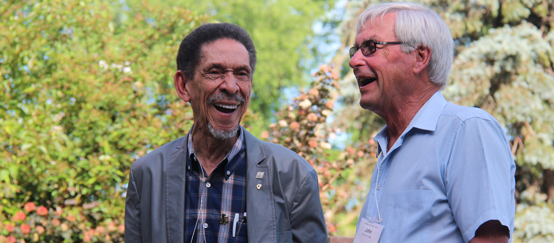 Two men laugh together outside at an alumni reunion