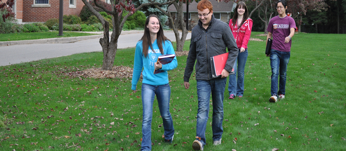 Two female and two male students walk on campus green during fall