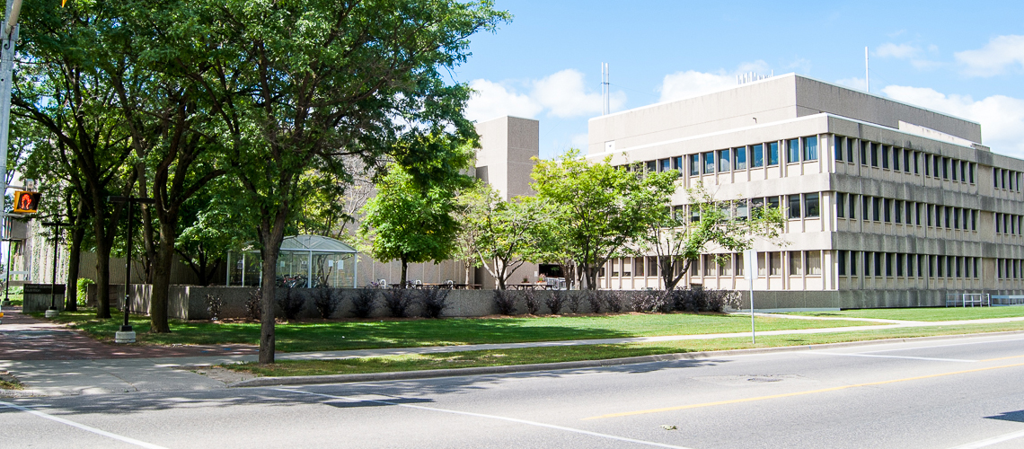 Image of grey Animal Nutrition building from across the street, trees to the left