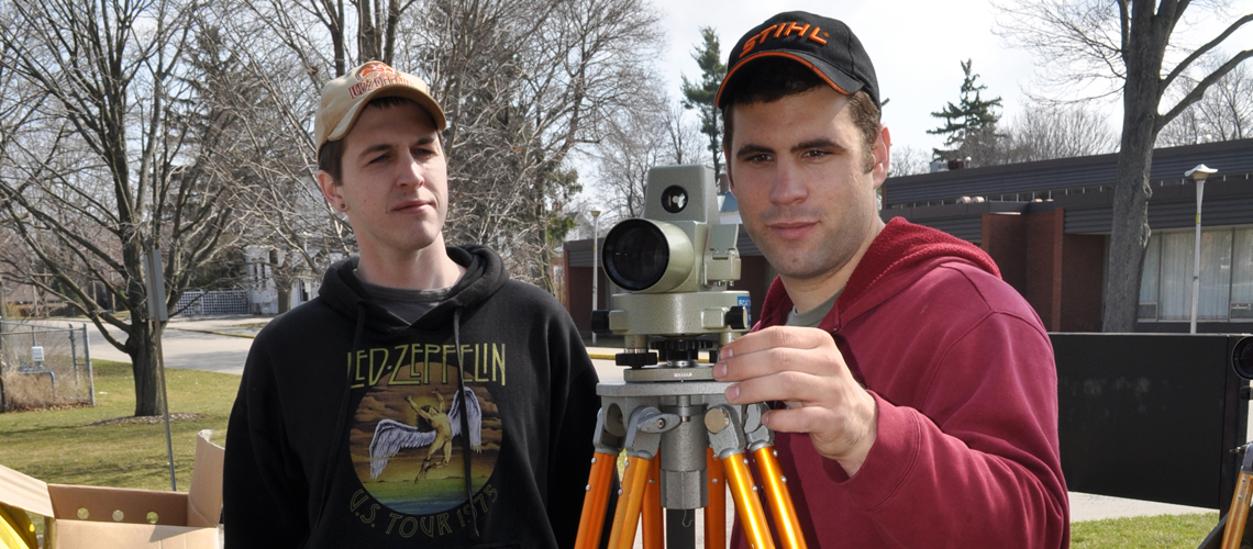 Two male students using a surveying device