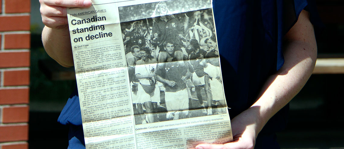Tara holding newspaper clipping from 1991 Globe and Mail featuring a photo of her at the games