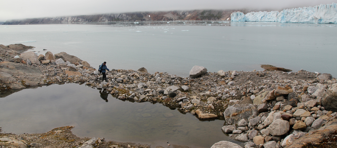 Hiker walking on rocky ground near icy water