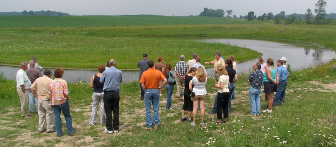 Community members stand in swampy grasslands