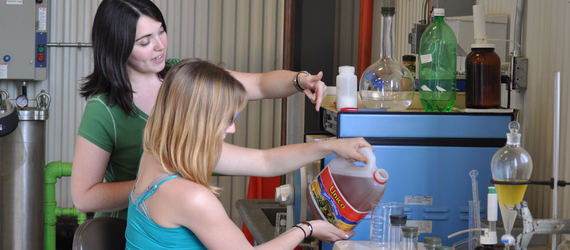 One female student shows another how to pour oil into a beaker
