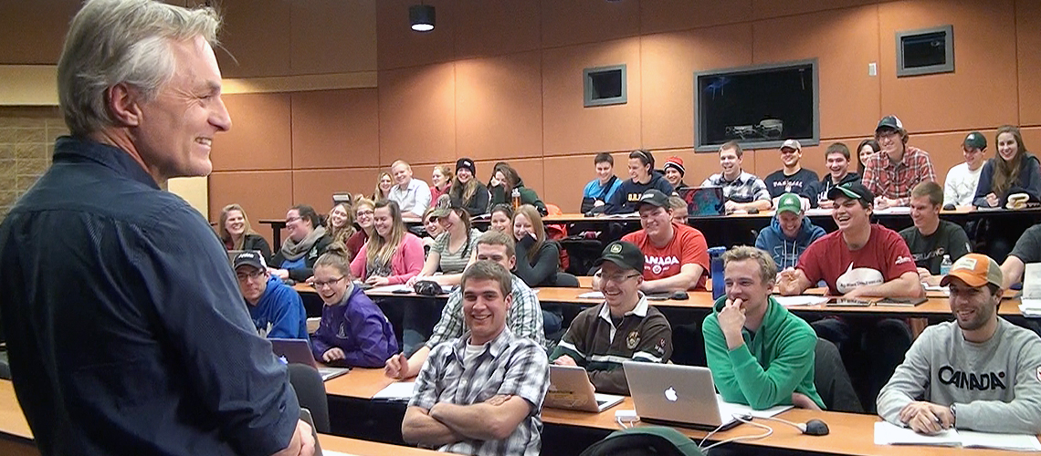 Male professor speaks to class of smiling students in lecture hall
