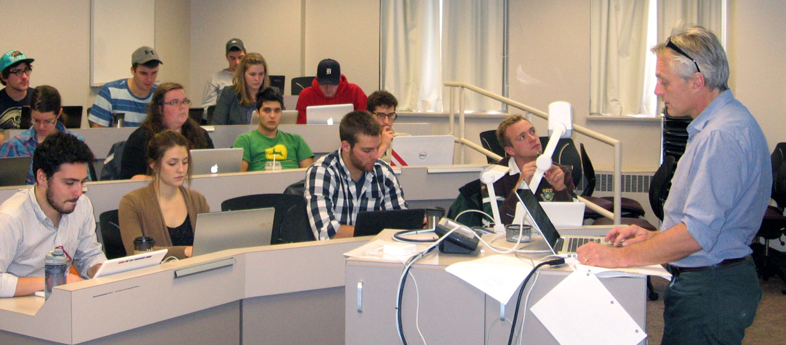 Small class of students look to professor speaking from podium at the front of a classroom