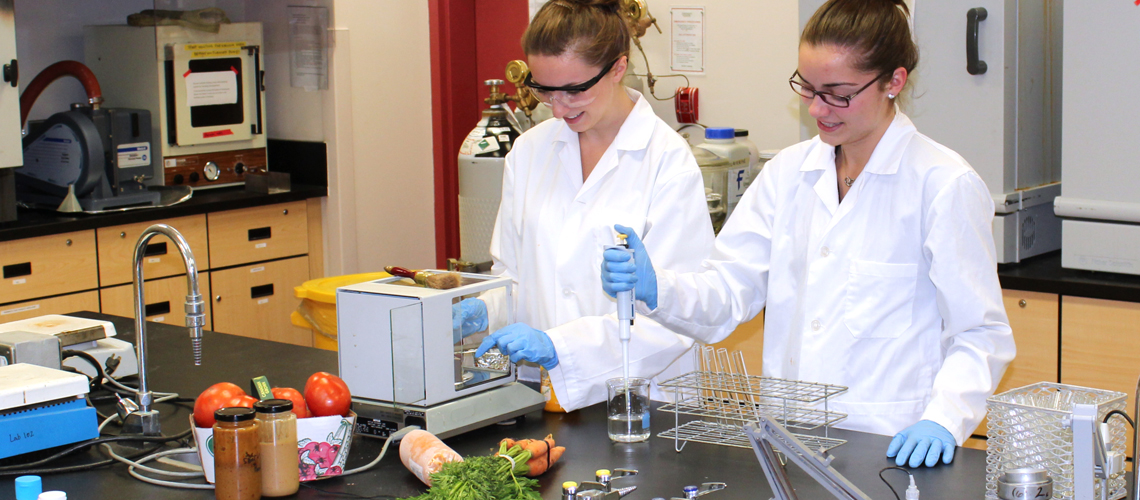 Two female students in lab coats and blue gloves take samples of food in lab