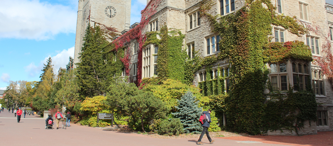Side angle of Johnston Hall covered in vines. Students walking around.