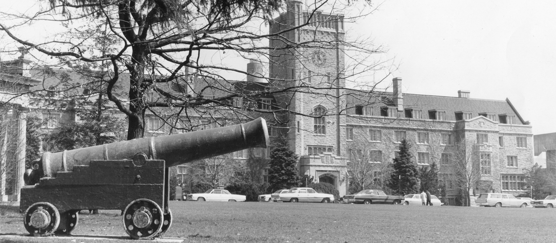 Black and white photo of cannon in front of Johnston Hall