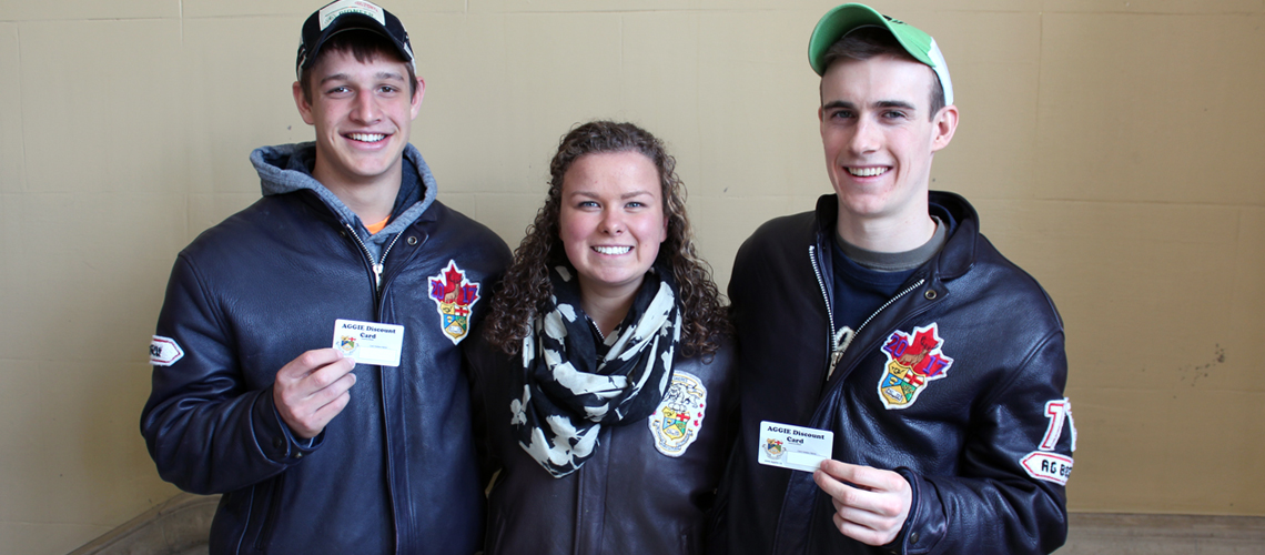 Two male and one female student stand together all wearing matching leather jackets and holding up membership cards