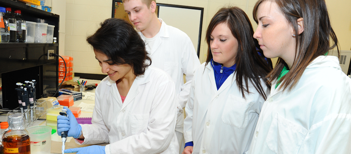 Three students watch technician take sample in lab, all wearing lab coats