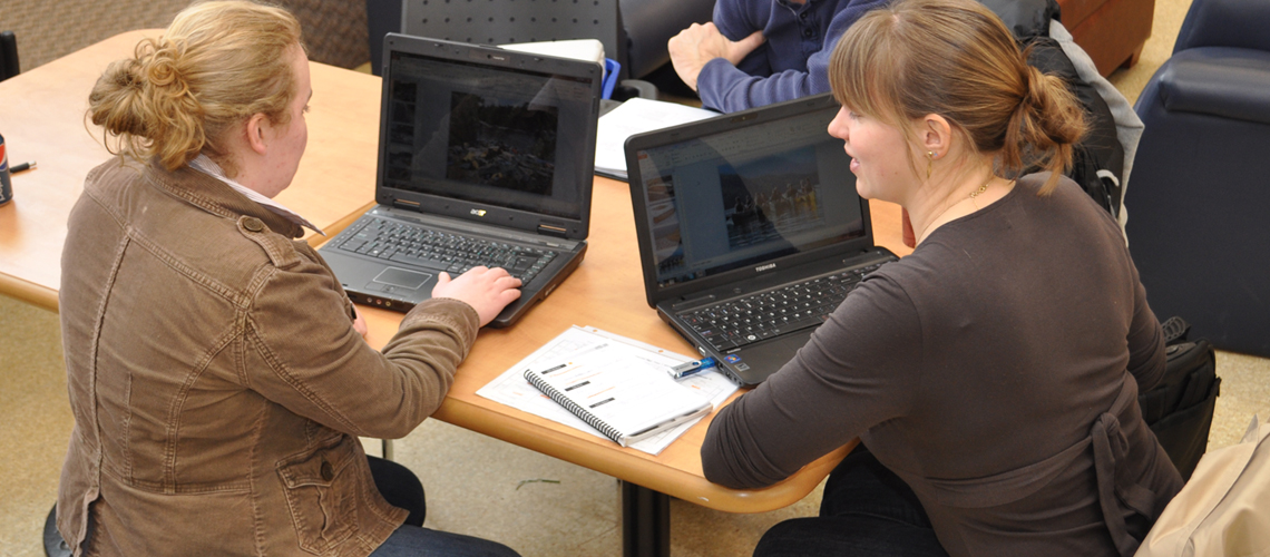 Two female students sit with laptops, backs to the camera