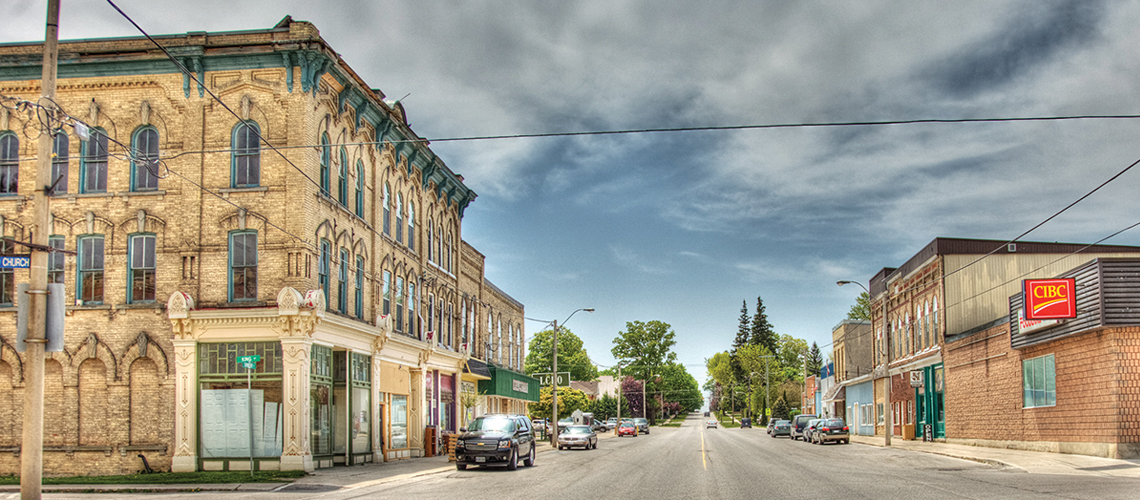 Photo of a car-lined street with old building on left and CIBC bank on right.