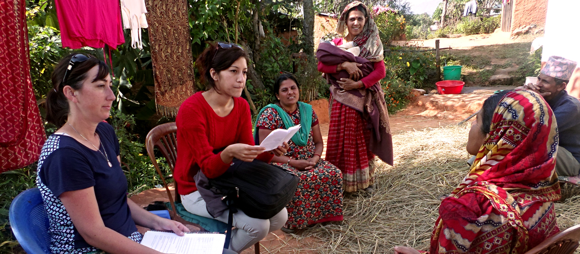 Woman and interpreter interview rural citizens outside of their home.