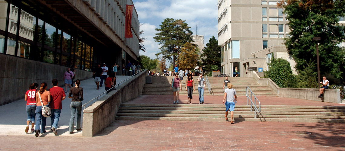 Many students walking on red brick walkway with stairs