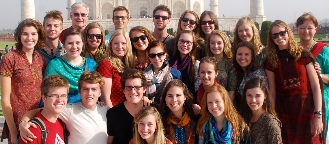 Group of students and professors stand together in front of the Taj Mahal in India