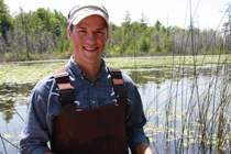 Joshua Persi stands in overalls in a large pond.