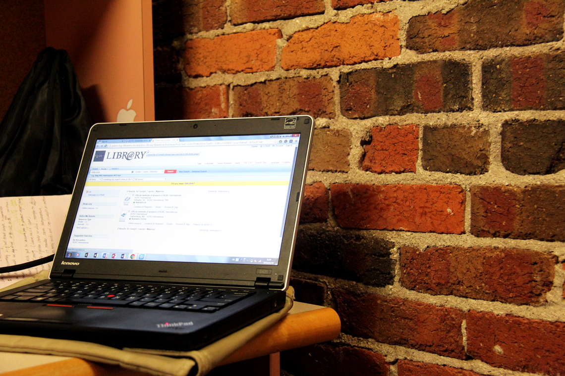Laptop open on a desk against a brick wall.