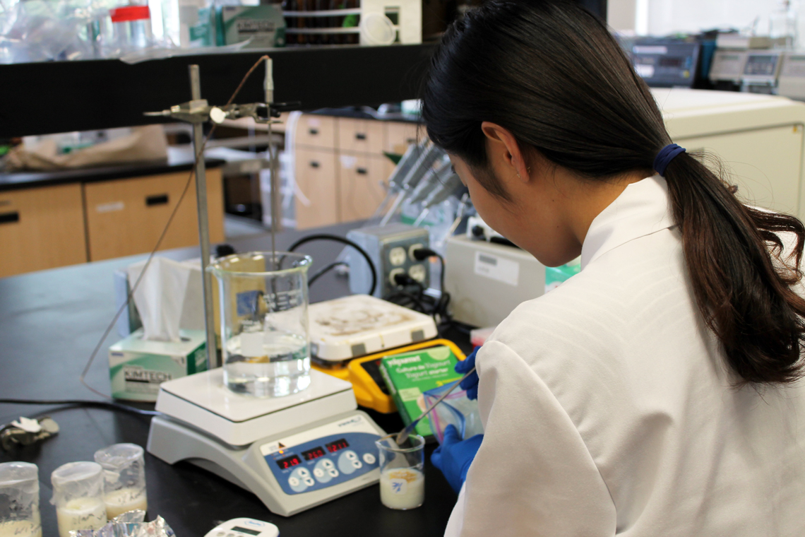 Xinya works in the lab, mixing and measuring samples in beakers.