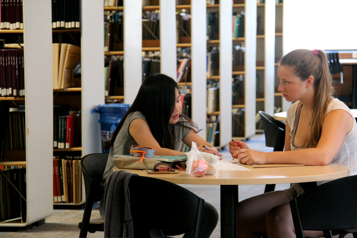 Xinya talks with an undergraduate student at a table in the library.