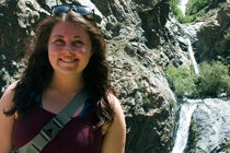 Laura Stortz stands in front of a small waterfall.
