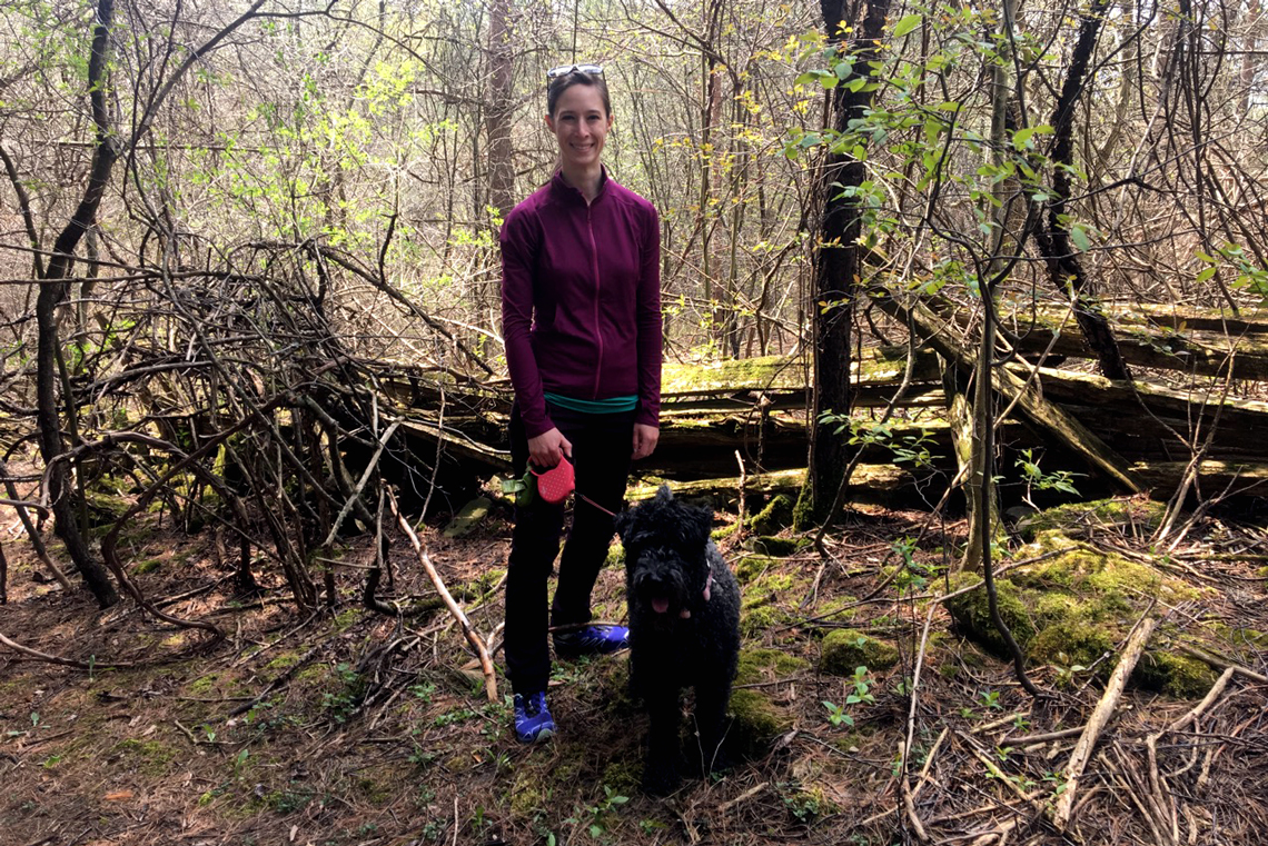 Lauren stands with her dog on a trail in the forest.