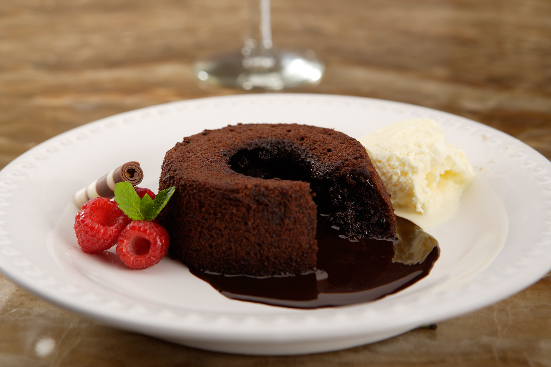 Chocolate cake, with chocolate syrup oozing from centre, on white plate