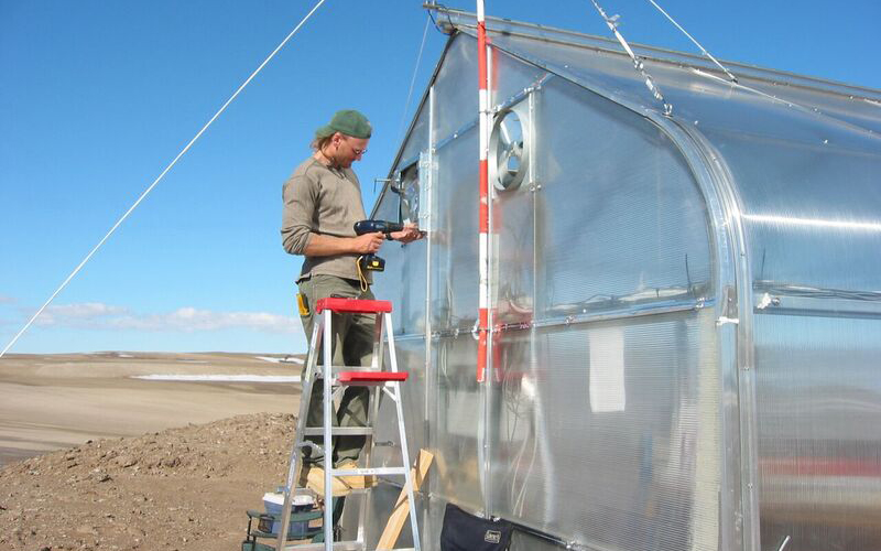 Tom standing on ladder and drilling into the side of a large greenhouse structure