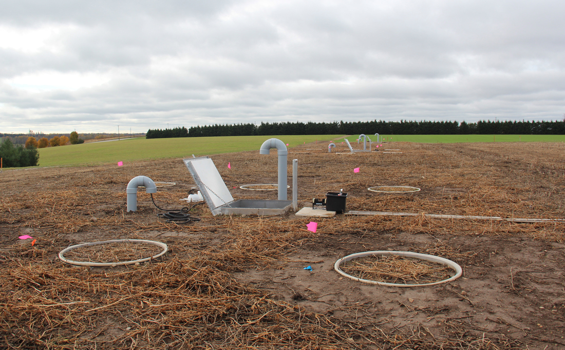 Bare field with circles, pipes, censors and pink flags sticking out.