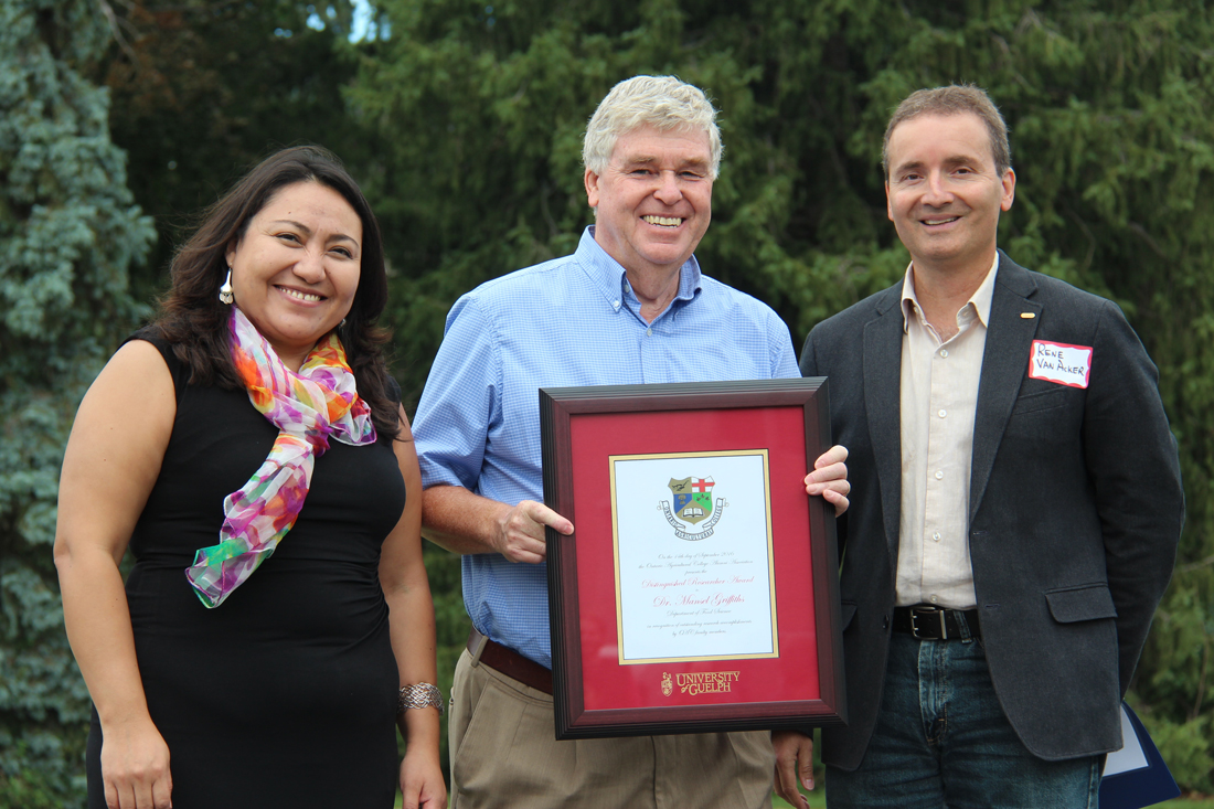 Rocio Morales Rayas, Mansel Griffiths and Rene Van Acker pose outside with framed certificate